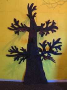 Fix large a tree to wall, mine is a partition wall so a staple gun was good. I made the tree from corrugated card, glue gun sticks and brown acrylic paint. See link to find out more. https://lizzymason.com/2014/10/25/make-a-3d-tree-for-a-wall-display-seasonal-decorations/