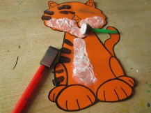 Print & Cut out tiger template onto orange card and fold in half the main body. Paint on stips and belly as shown.