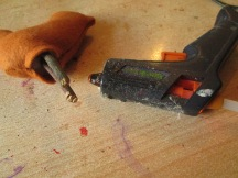Fill timb hole with glue from glue gun and stick in two sticks for legs, hold for setting.