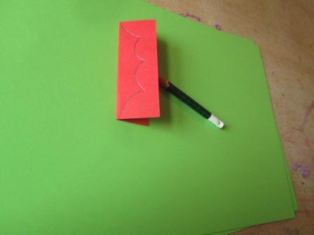 Cut and fold a small scarp piece of cad about 9cm x 6cm. Daw half a holly leaf as shown.